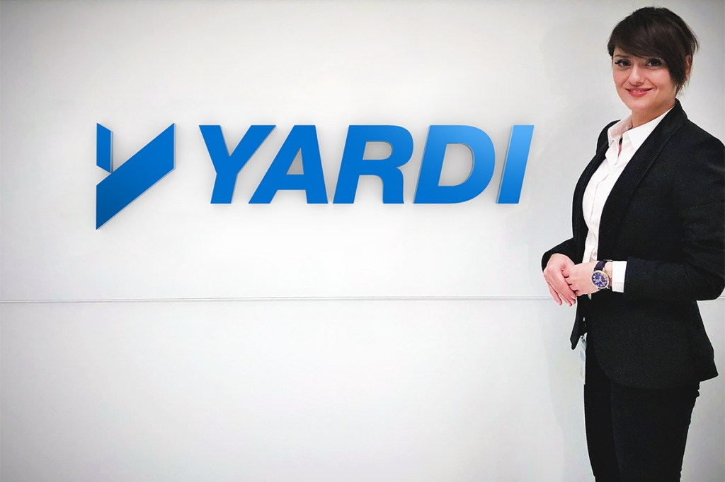 Parisa Vafaei next to Yardi sign